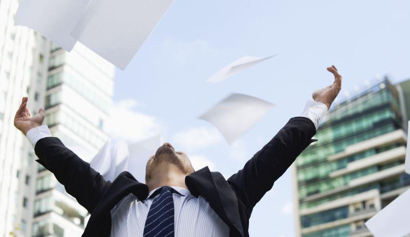 Businessman thrwoing paper in air